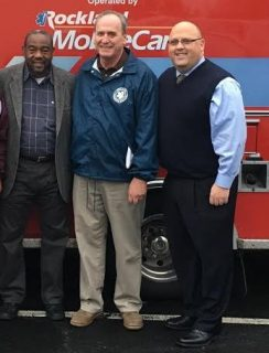 L-R: Renold Julien, Ray Florida, and Pat Withers stand in front of the ambulance being donated to the Haiti relief efforts.