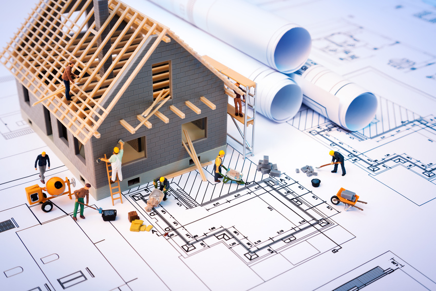 building house on blueprints with worker – construction project